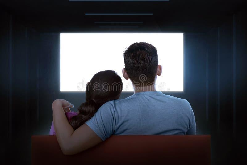 Retrato dos pares asiáticos que sentam-se no sofá que olha a tevê vazia fotos de stock