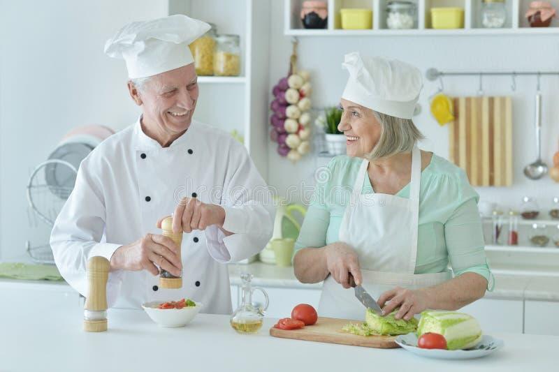 Retrato dos pares de cozinheiros chefe superiores de sorriso na cozinha foto de stock