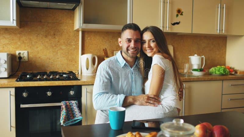 Retrato dos pares de sorriso felizes que sittting no amanhecer da cozinha em casa imagem de stock royalty free