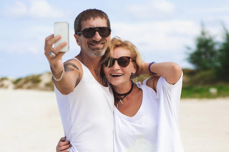 Retrato dos pares de sorriso maduros que tomam um selfie na praia foto de stock royalty free