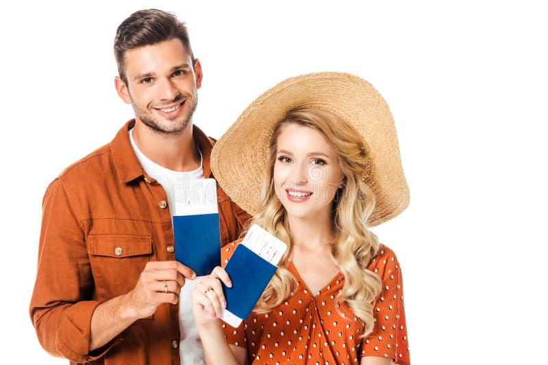 retrato dos pares de sorriso que mostram passaportes e bilhetes nas mãos foto de stock