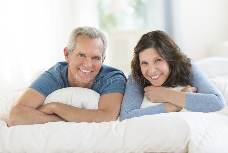 Retrato dos pares felizes que encontram-se junto na cama imagens de stock royalty free