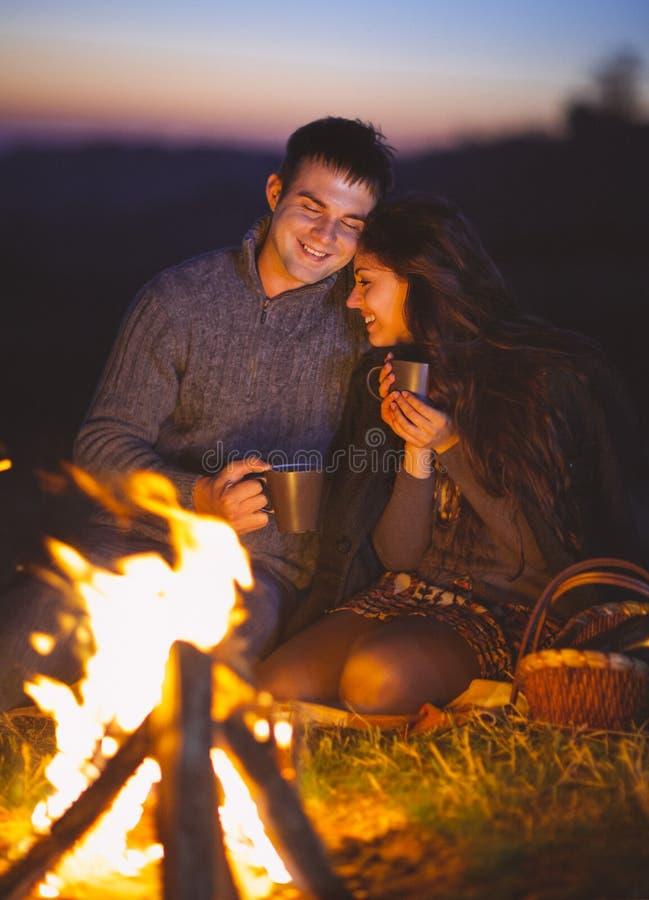 Retrato dos pares felizes que sentam-se pelo fogo na praia do outono fotos de stock royalty free
