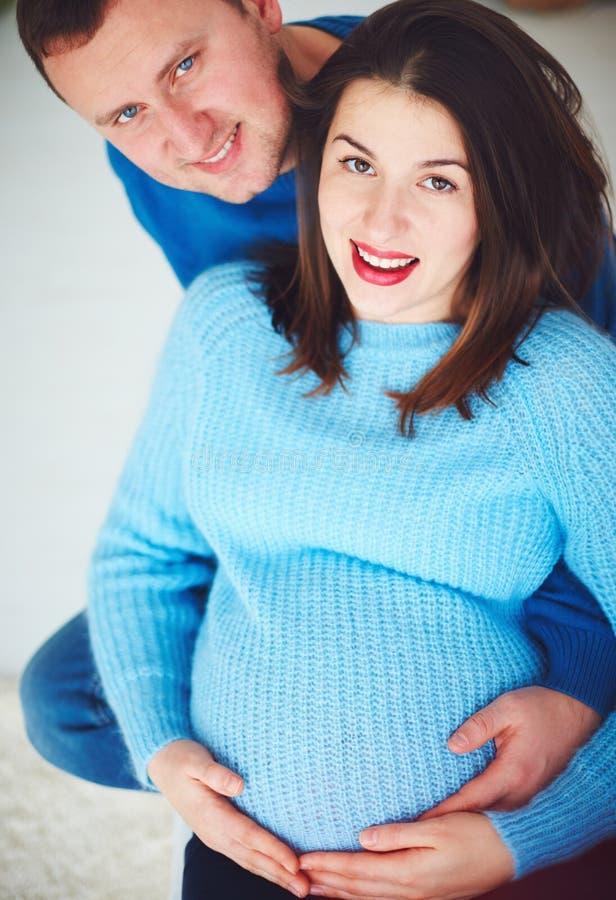 Retrato dos pares grávidos felizes que relaxam em casa imagens de stock royalty free