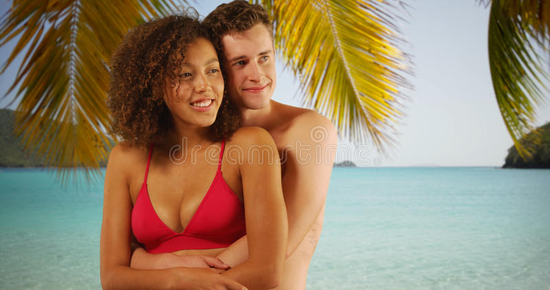 Retrato dos pares inter-raciais bonitos que abraçam-se sob a palmeira foto de stock