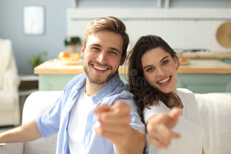 Retrato dos pares novos bonitos que apontam e que riem, sentando-se no sofá foto de stock royalty free