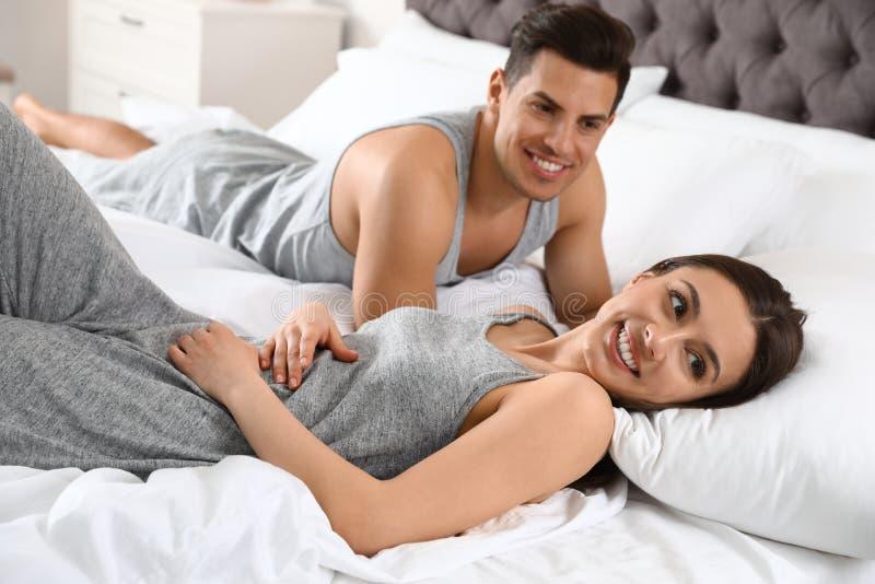 Retrato dos pares novos bonitos que descansam na cama fotografia de stock