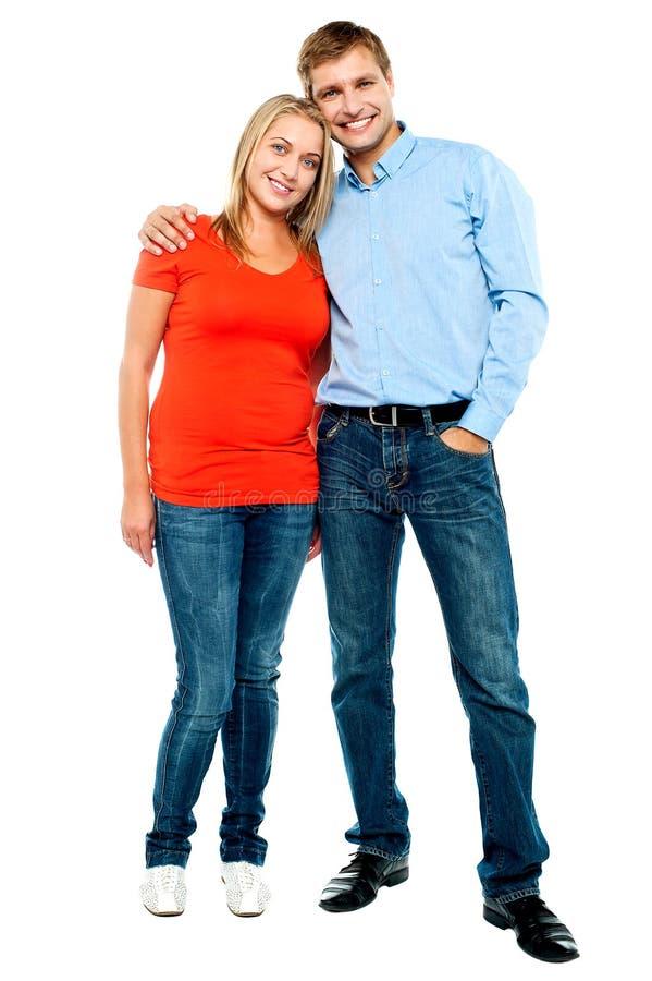 Retrato dos pares novos felizes que abraçam no estúdio foto de stock royalty free