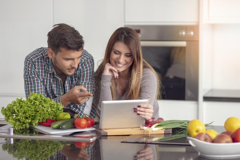 Retrato dos pares novos felizes que cozinham junto na cozinha em casa fotografia de stock royalty free