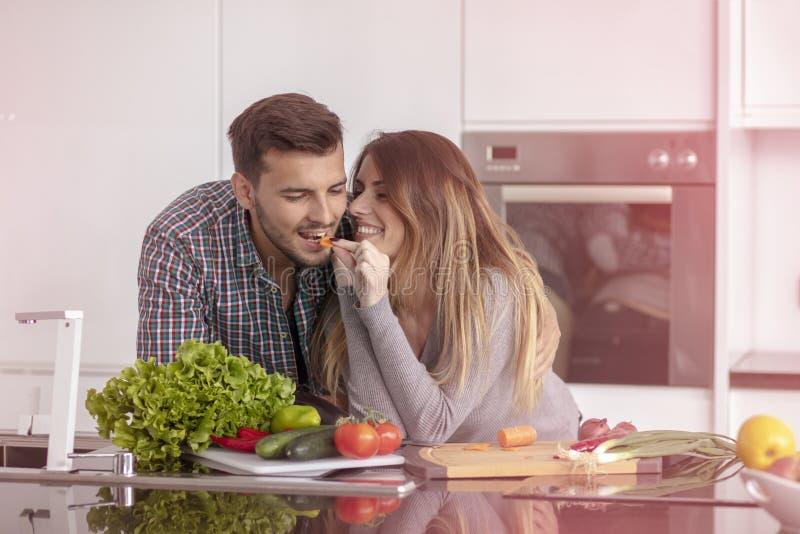 Retrato dos pares novos felizes que cozinham junto na cozinha em casa foto de stock