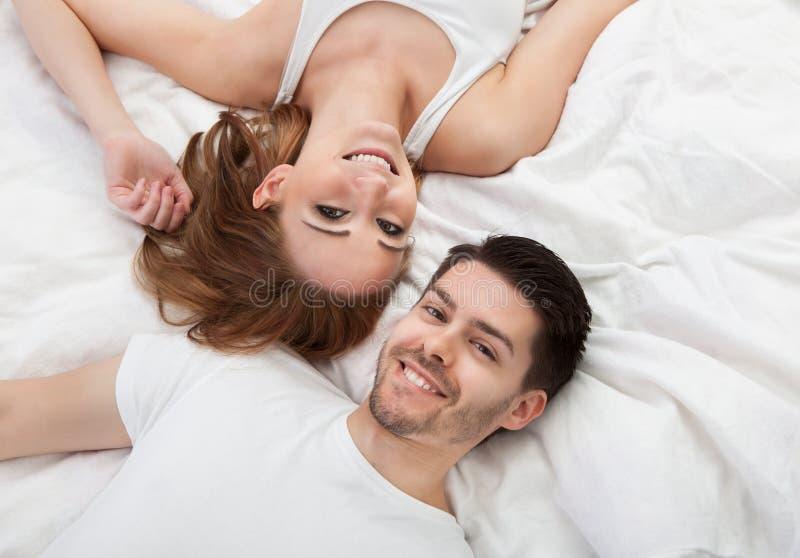 Retrato dos pares novos felizes que encontram-se na cama foto de stock royalty free