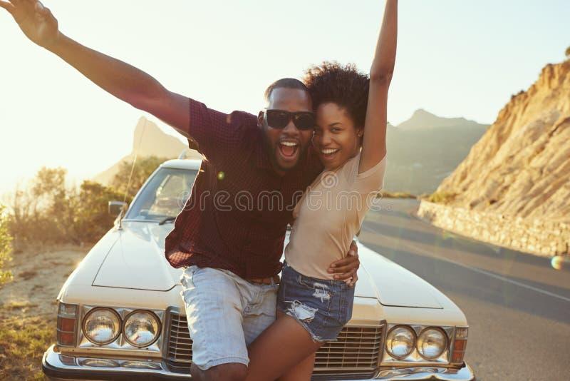 Retrato dos pares novos que estão ao lado do carro clássico foto de stock royalty free