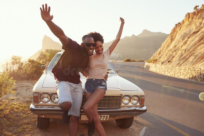 Retrato dos pares novos que estão ao lado do carro clássico imagem de stock