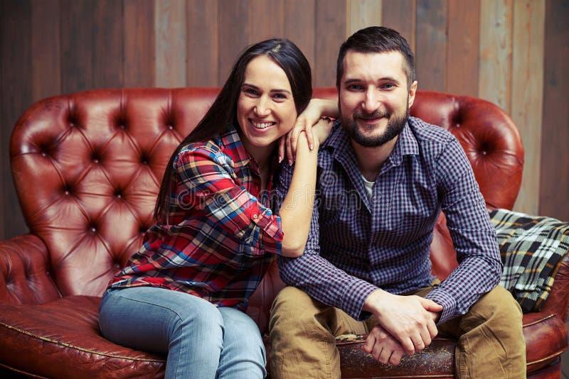 Retrato dos pares novos que sentam-se no sofá imagens de stock