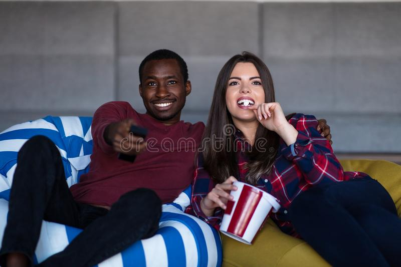 Retrato dos pares novos que sentam-se no sof? que olha um filme com express?o em suas caras imagem de stock