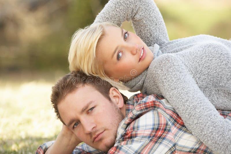 Retrato dos pares novos românticos que encontram-se na grama fotos de stock