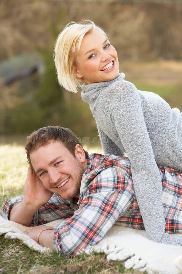 Retrato dos pares novos românticos que encontram-se na grama foto de stock royalty free