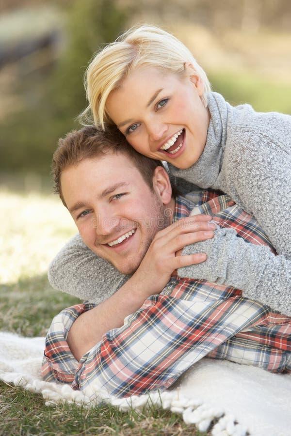 Retrato dos pares novos românticos que encontram-se na grama imagem de stock royalty free