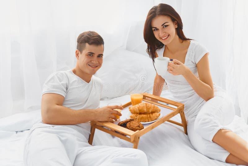 Retrato dos pares que apreciam o café da manhã na cama fotografia de stock