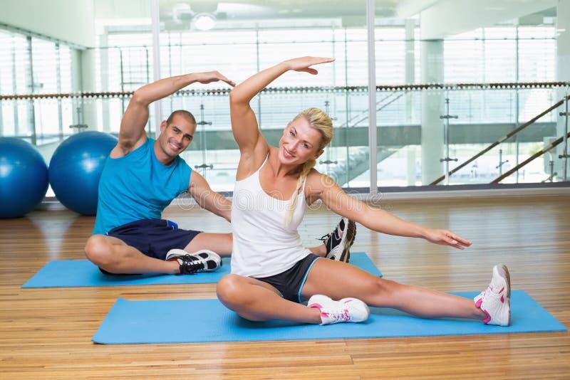 Retrato dos pares que esticam as mãos na classe da ioga imagens de stock