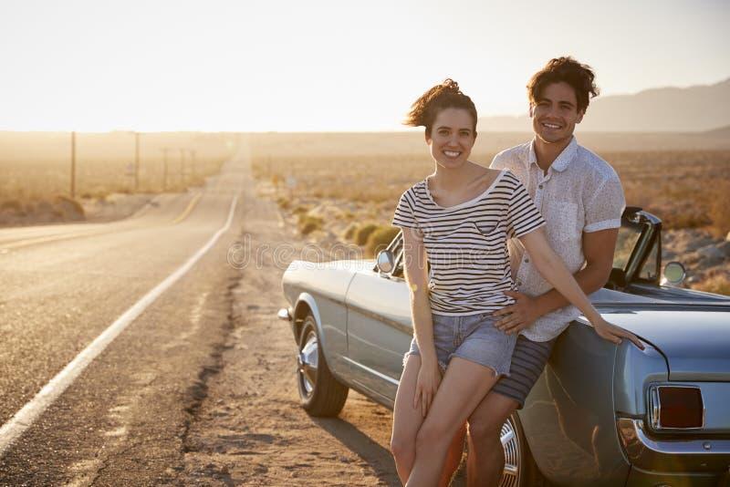 Retrato dos pares românticos que apreciam a viagem por estrada no carro clássico foto de stock