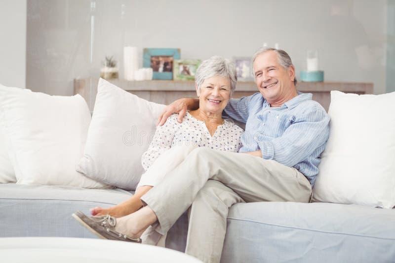 Retrato dos pares superiores românticos que sentam-se no sofá na sala de visitas fotografia de stock