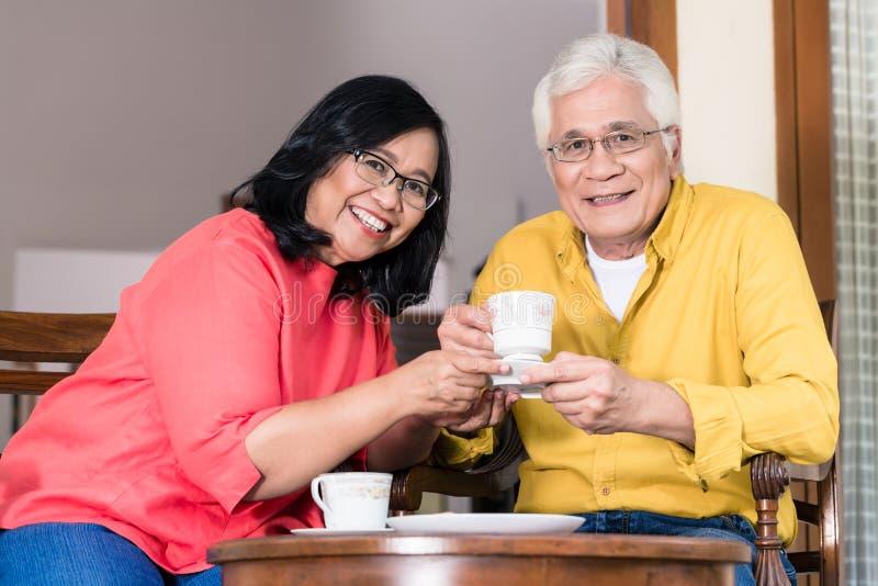Retrato dos pares superiores serenos que apreciam uma xícara de café no hom imagens de stock