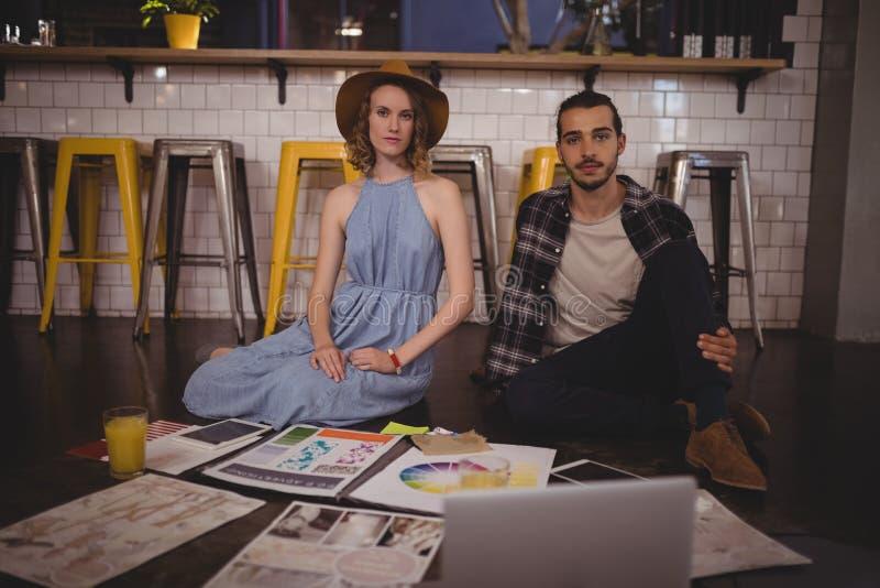 Retrato dos profissionais criativos novos que sentam-se no assoalho com papéis fotos de stock royalty free