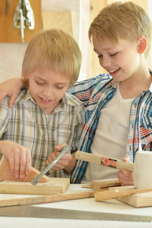 Retrato dos rapazes pequenos bonitos que trabalham com madeira na oficina foto de stock