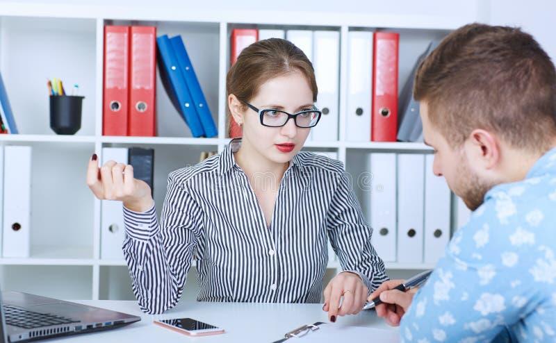 Retrato dos sócios comerciais espertos novos que comunicam-se na reunião fotos de stock