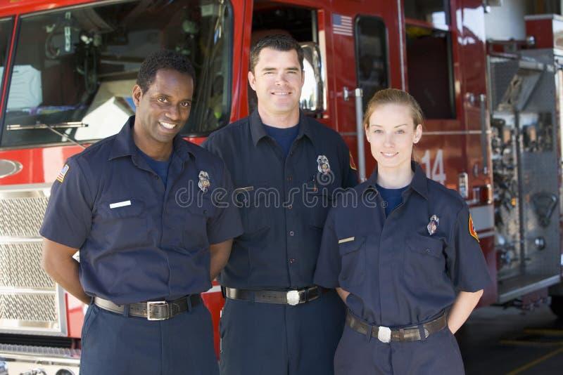 Retrato dos sapadores-bombeiros que estão por um motor de incêndio foto de stock