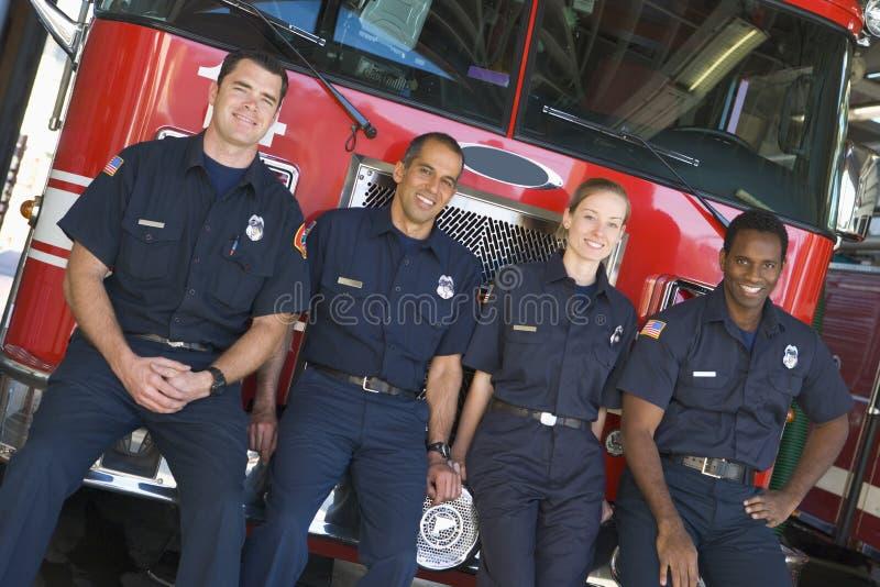 Retrato dos sapadores-bombeiros que estão por um motor de incêndio fotos de stock royalty free