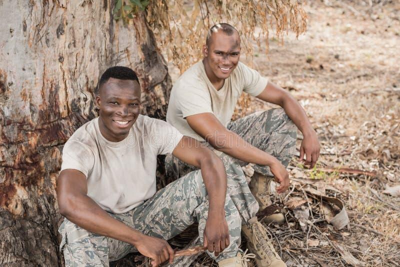 Retrato dos soldados militares que relaxam durante o treinamento do obstáculo imagem de stock