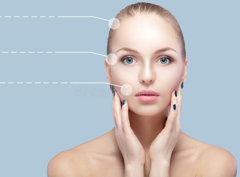Retrato dos termas da mulher nova e natural com as setas pontilhadas na cara no fundo azul Medicina e cuidados com a pele imagens de stock