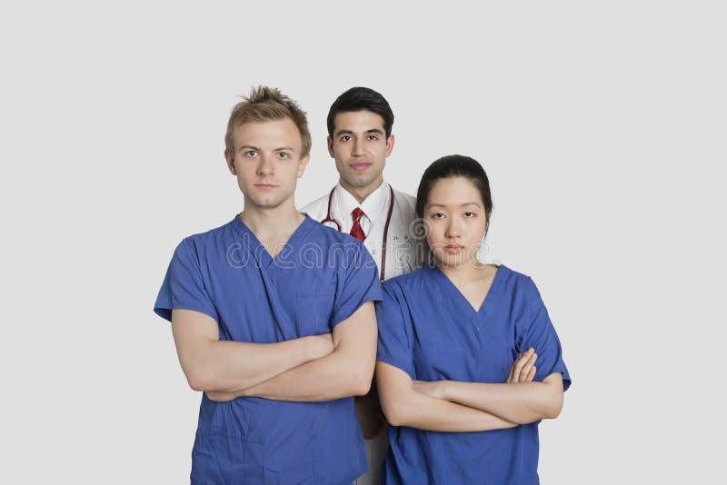 Retrato dos trabalhadores seguros dos cuidados médicos que estão sobre o fundo cinzento fotografia de stock royalty free