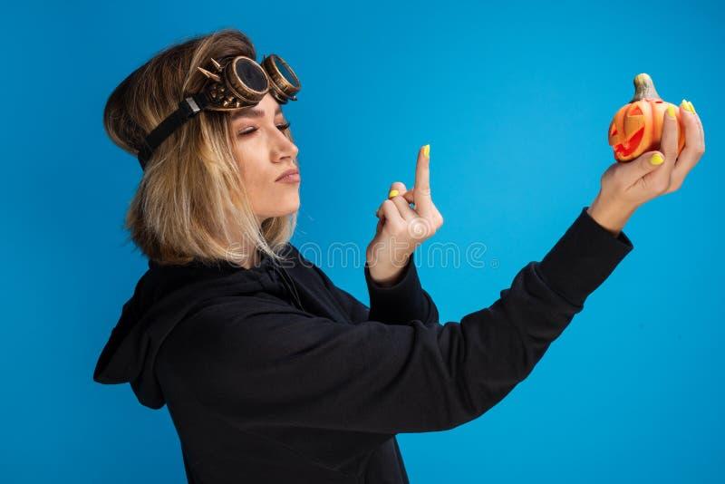 Retrato dos vidros punk vestindo do vapor da menina do goth que indicam um dedo obsceno em uma abóbora cinzelada de Helloween fotografia de stock