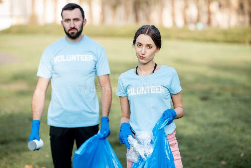 Retrato dos voluntários com os sacos dos desperdícios no parque imagens de stock