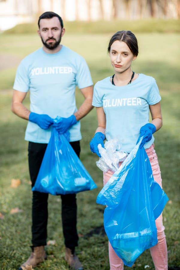 Retrato dos voluntários com os sacos dos desperdícios no parque imagens de stock royalty free
