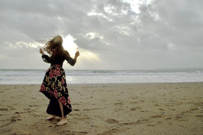 Retrato dramático de la señora de pelo largo en vestido formal floral en una playa tempestuosa delante del sol foto de archivo