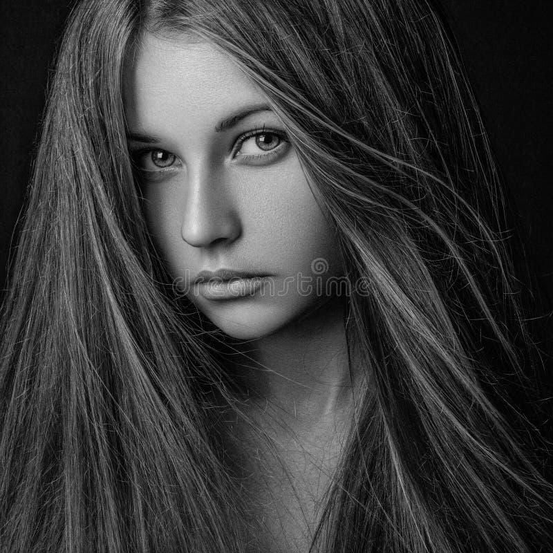 Retrato dramático de um tema da menina: retrato de uma menina só bonita com cabelo do voo no vento isolado no fundo escuro dentro foto de stock royalty free