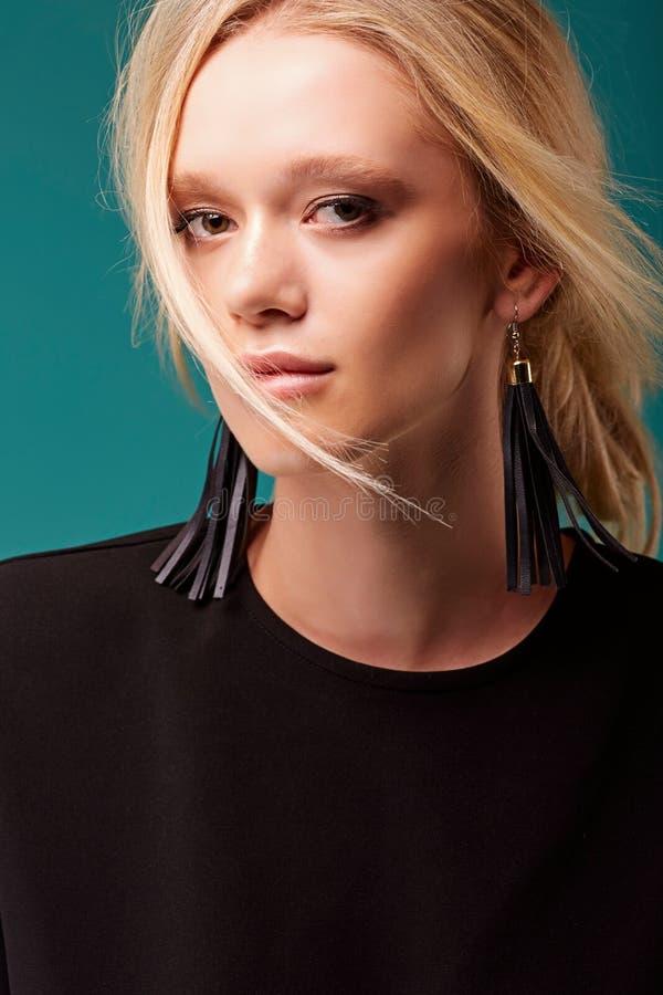 Retrato dramático de uma menina bonita nova em um vestido preto em um fundo azul no estúdio imagens de stock royalty free