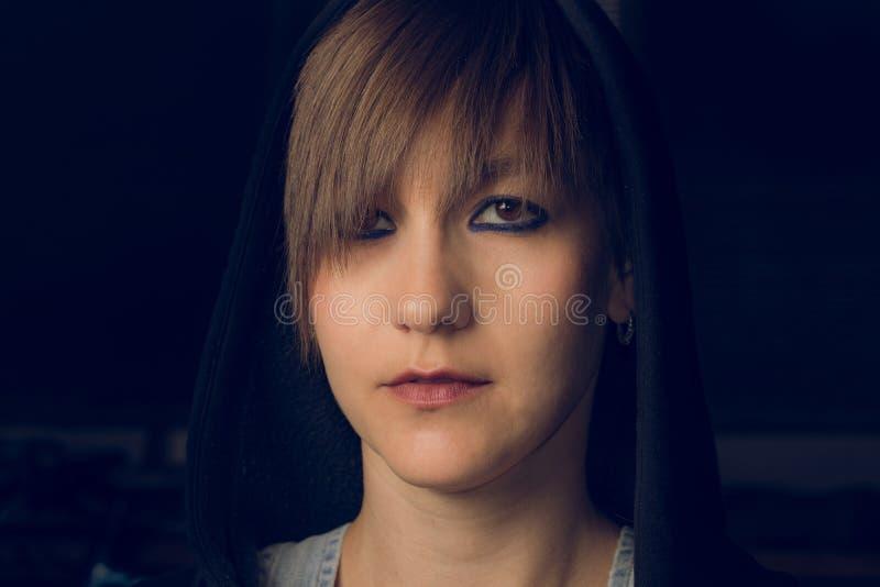 Retrato dramático de una muchacha en una sudadera con capucha imagenes de archivo