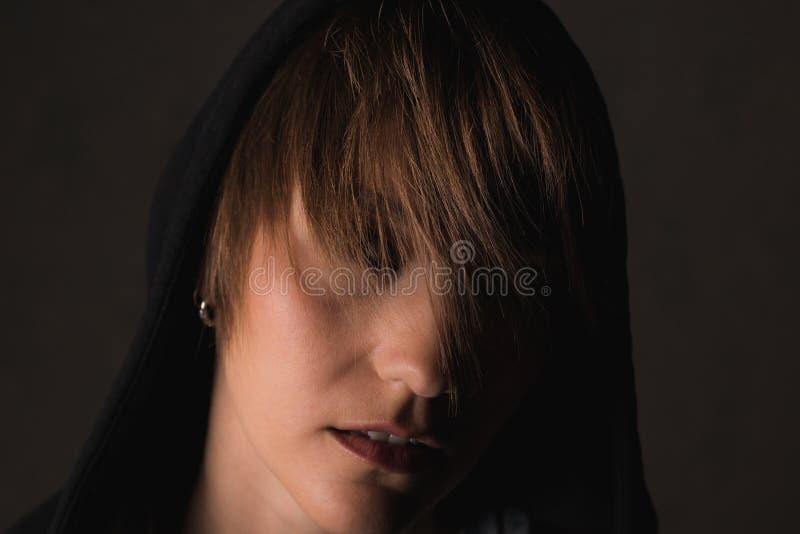 Retrato dramático de una muchacha en una sudadera con capucha foto de archivo