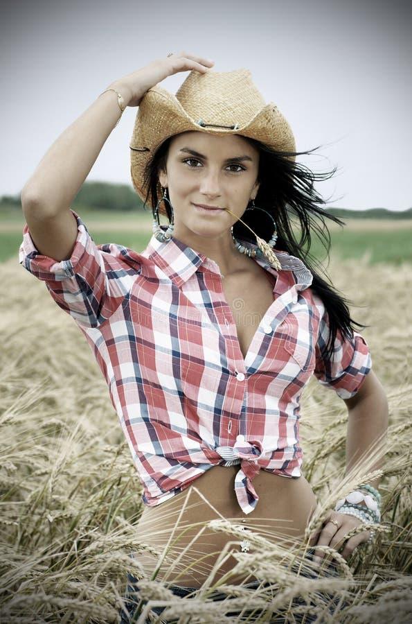 Retrato dramático del cowgirl bonito en campo de trigo imagenes de archivo
