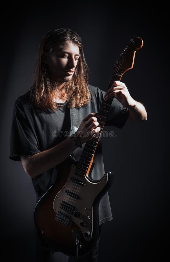 Retrato dramático del estudio: músico hermoso de la roca del hombre joven con el pelo largo que toca la guitarra eléctrica fotos de archivo libres de regalías