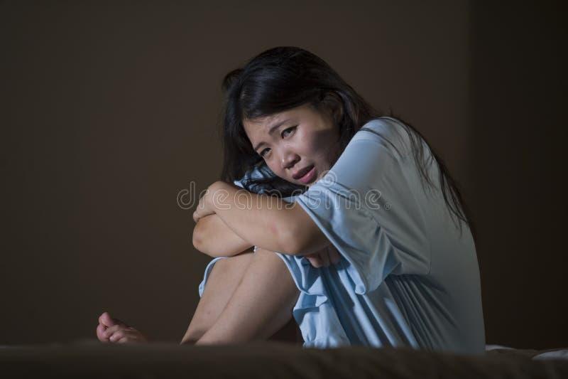 Retrato dramático del griterío chino asiático hermoso y triste joven de la mujer desesperado en la cama despierta en la depresión foto de archivo libre de regalías