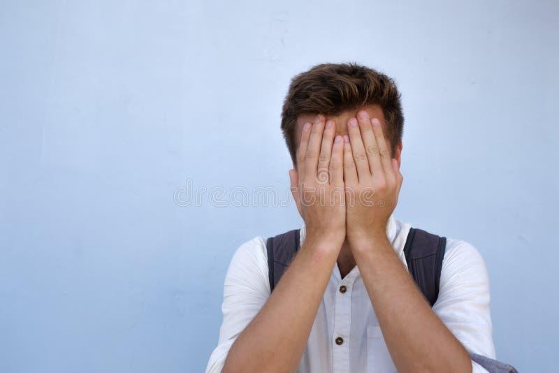 Retrato dramático del hombre triste desesperado en fondo azul Él está ocultando su cara fotos de archivo libres de regalías