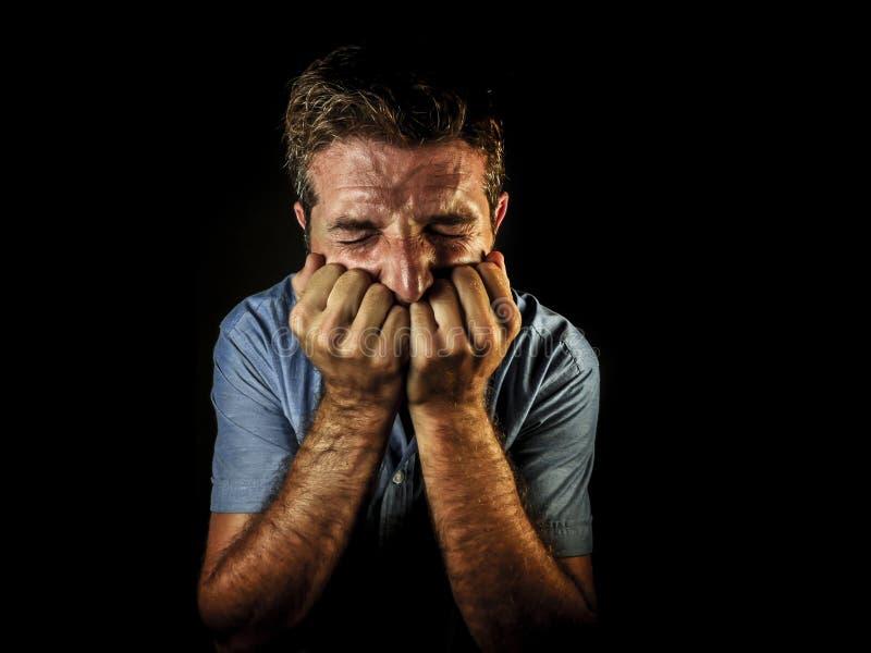 Retrato dramático del hombre triste y deprimido atractivo con las manos en su depresión y dolor sufridores desesperados gritadore fotografía de archivo