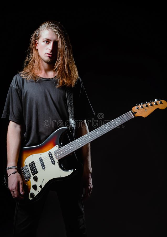 Retrato dramático do estúdio: músico de cabelos compridos considerável da rocha do homem novo com guitarra elétrica fotos de stock