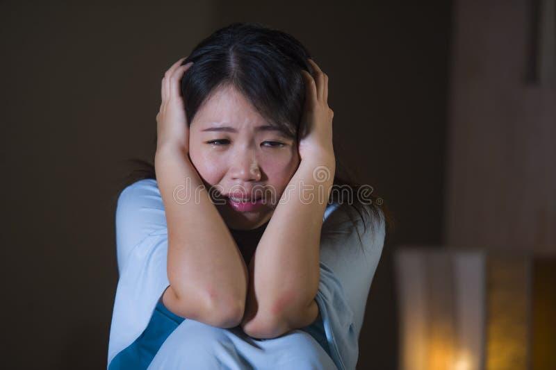 Retrato dramático do grito japonês asiático bonito e triste novo da mulher desesperado na cama acordada na depressão do sofriment fotografia de stock royalty free